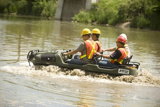 Вездеход Арго плывет по реке с четырьмя людьми на борту